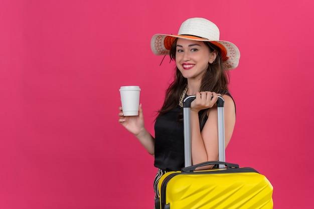 Glimlachend reiziger jong meisje, gekleed in zwart onderhemd in hoed met koffer met kopje koffie op rode achtergrond