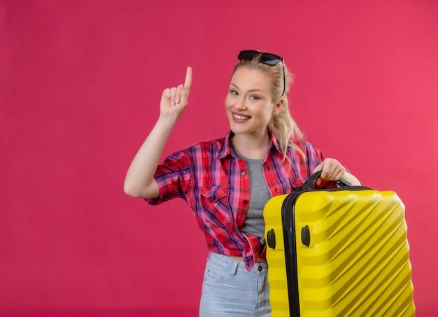 Glimlachend reiziger jong meisje met rood shirt en bril op haar hoofd met koffer wijst naar omhoog op geïsoleerde roze achtergrond