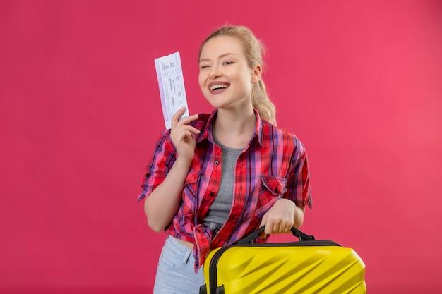 Glimlachend reizigers jong meisje die de rode koffer en het kaartje van de overhemdsholding op geïsoleerde roze achtergrond dragen