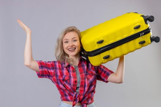 Glimlachend reizigers jong meisje die de rode koffer van de overhemdsholding op schouder op geïsoleerde witte achtergrond dragen