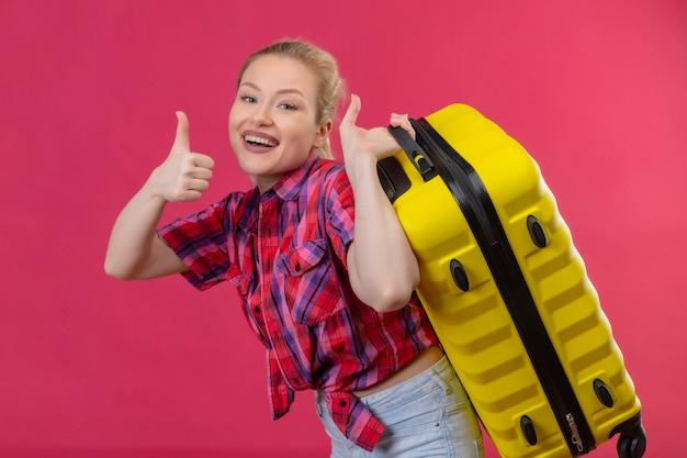 Glimlachend reizigers jong meisje die rood overhemd dragen die soitcase op rug haar duim op geïsoleerde roze achtergrond houden