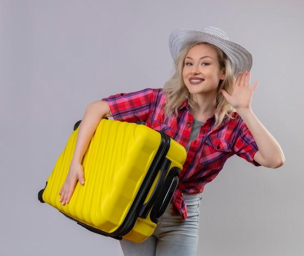 Glimlachend reizigers jong meisje die rood overhemd in de koffer van de hoedenholding dragen die luistergebaar op geïsoleerde witte achtergrond tonen