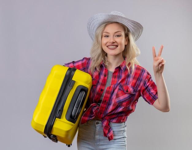 Glimlachend reizigers jong meisje die rood overhemd in de koffer van de hoedenholding dragen die vredesgebaar op geïsoleerde witte achtergrond tonen