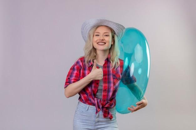 Glimlachend reizigers jong meisje die rood overhemd in hoed dragen die opblaasbare ring haar duim op geïsoleerde witte achtergrond houden