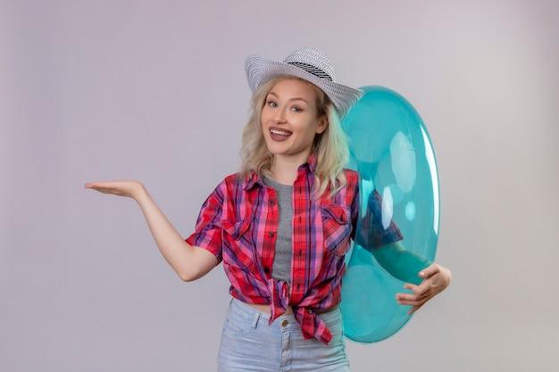 Glimlachend reizigers jong meisje die rood overhemd in hoed dragen die opblaasbare ring houden wijst naar kant op geïsoleerde witte achtergrond