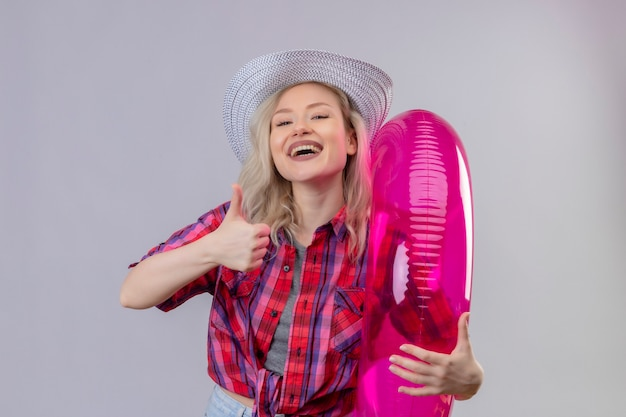 Glimlachend reizigers jong meisje die rood overhemd in hoed dragen die opblaasbare ring op geïsoleerde witte achtergrond houden