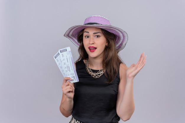 Glimlachend reizigers jong meisje die zwart onderhemd dragen in de kaartjes van de hoedenholding op witte achtergrond