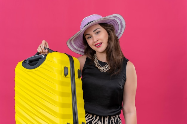 Glimlachend reizigers jong meisje die zwart onderhemd dragen in de koffer van de hoedenholding op rode achtergrond