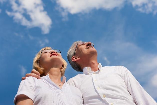 Glimlachend rijp paar dat de blauwe hemel onderzoekt