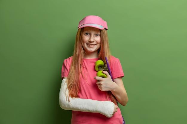 Glimlachend roodharig meisje heeft een ongeluk gehad na het berijden van een skateboard, draagt gips of gips op een gebroken arm, blijft gelukkig, raakte geblesseerd tijdens favoriete sport, staat tegen een groene muur. kinderen, gezondheidszorg