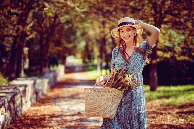 Glimlachend roodharig meisje loopt alleen in het herfstpark op een zonnige warme dag terwijl ze in de zomer een handtas vasthoudt