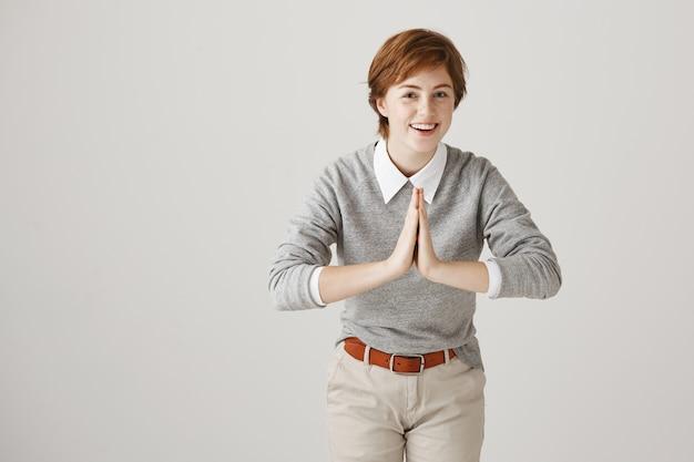 Glimlachend roodharig meisje met kort kapsel poseren tegen de witte muur