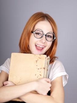 Glimlachend roodharig meisje met oud boek.