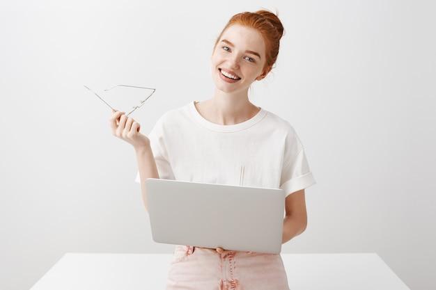 Glimlachend roodharigemeisje die laptop met behulp van en kijken