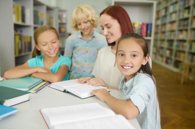 Glimlachend schattig donkerharig schoolmeisje dat aan het bureau zit met haar klasgenoten en de vrouwelijke leraar in een openbare bibliotheek