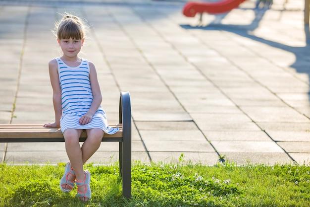 Glimlachend schattig jong meisje zit alleen buitenshuis op een bankje