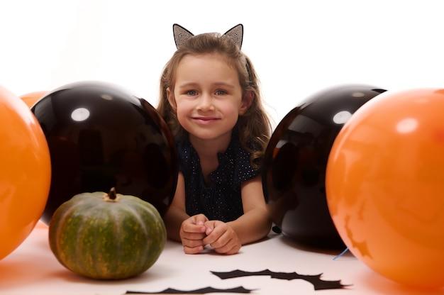 Glimlachend schattig kind meisje in carnaval kostuum, kleine heks liggend op een witte achtergrond met kopie ruimte naast pompoenen, handgemaakte vleermuizen en kleurrijke oranje zwarte ballonnen. halloween-feestconcept