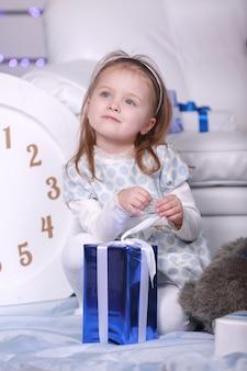 Glimlachend schattig klein meisje dat haar kerstcadeau houdt. grote witte klok en teddybeer op muur. viering nieuwjaar.