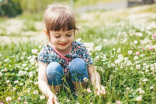 Glimlachend schattig klein meisje zittend op een klaverveld, genietend van de zomer