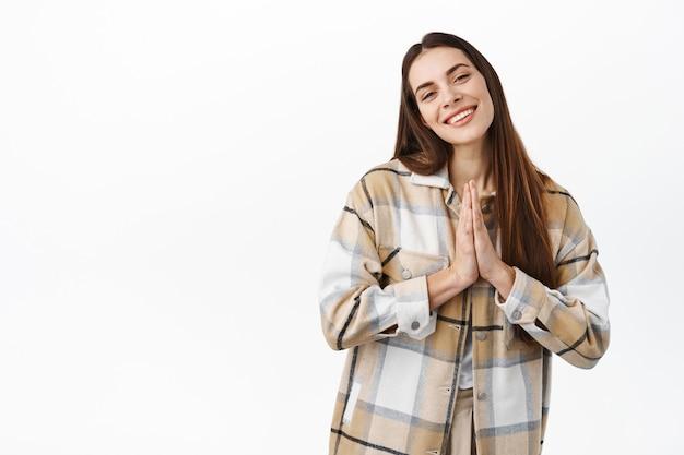 Glimlachend schattig meisje dat om gunst vraagt, laat een smeekgebaar zien en glimlach terughoudend, smekend, iets nodig, staande over een witte muur