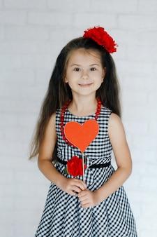 Glimlachend schattig meisje in geruite jurk met rode bloem in haar haar