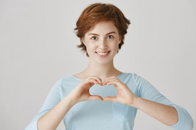 Glimlachend schattig roodharig meisje poseren tegen de witte muur