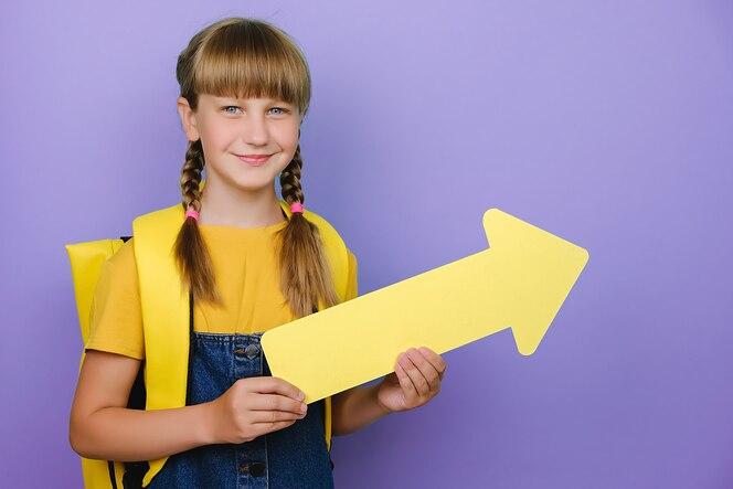 Glimlachend schattig schoolmeisje opzij met gele pijl, draagt rugzak, geïsoleerd poseren over paarse studio kleur achtergrond muur met kopie ruimte voor promotionele inhoud. terug naar schoolconcept