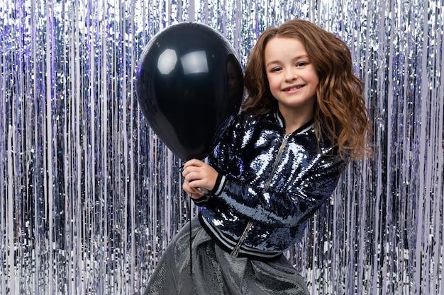 Glimlachend schattig stijlvolle kaukasische meisje in glanzende kleding met een zwarte ballon op een feestelijke klatergoud muur