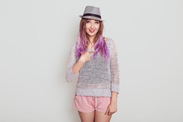Glimlachend schattig vrouwtje in hoed en wijzend naar zichzelf met wijsvinger, shirt en stijlvolle hoed dragen, geweldig zijn dat haar kiezen, geïsoleerd over witte muur.