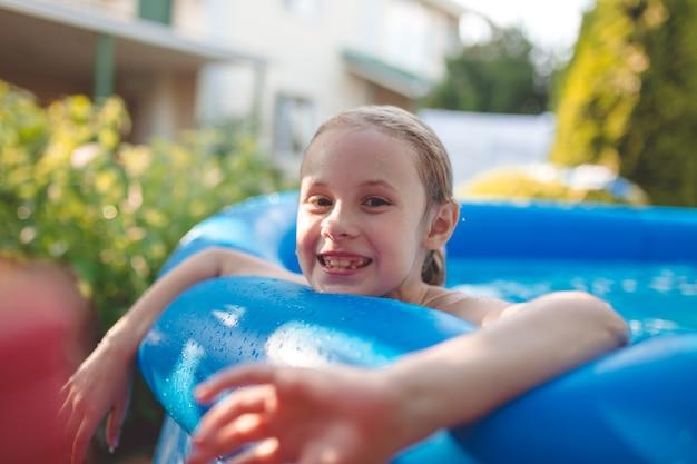 Glimlachend schattig zeven jaar oud meisje spelen en plezier hebben in opblaasbaar zwembad.