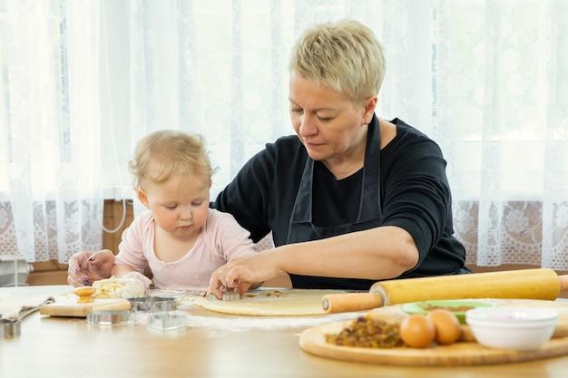 Glimlachend schattige babymeisje kneden van deeg voor koekjes in de keuken aan een houten tafel.