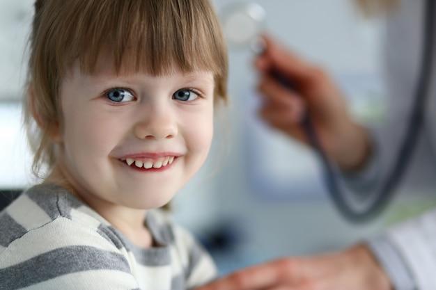 Glimlachend schattige kleine patiënt interactie met vrouwelijke arts