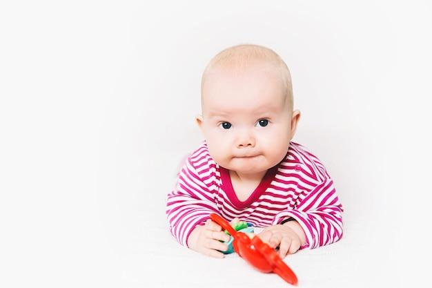 Glimlachend schattigste baby spelen met kleurrijk speelgoed gelukkig 6 maanden oud baby kind spelen en ontdekken