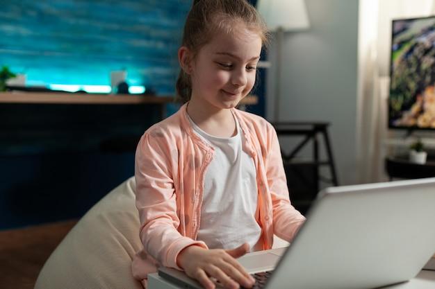 Glimlachend scholier browsen informatie op laptop werken op school huiswerk