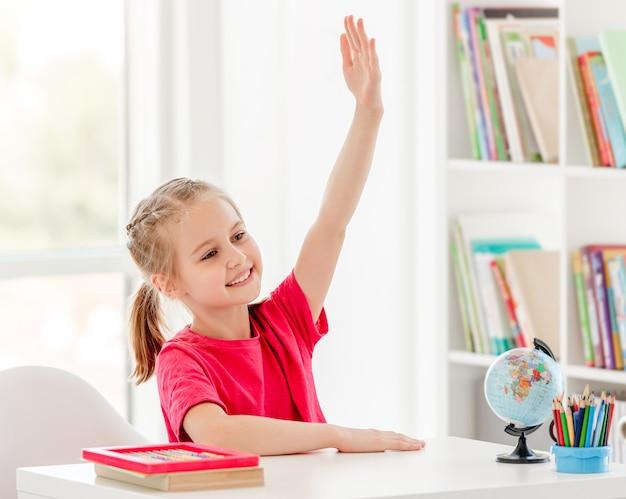 Glimlachend schoolmeisje dat hand opheft bereid om tijdens les te antwoorden