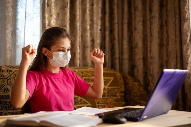 Glimlachend schoolmeisje dat in medisch masker thuis bestudeert. gelukkige leerling die thuis lessen heeft via internet, op laptop werkt, graag zijn taak correct uitvoert