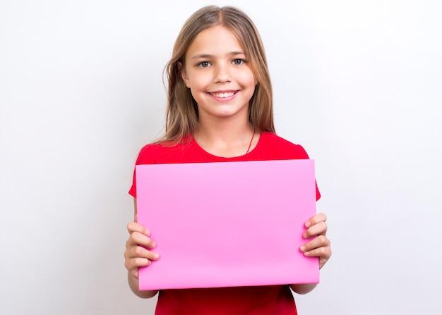 Glimlachend schoolmeisje dat leeg voorbeeldenboek toont