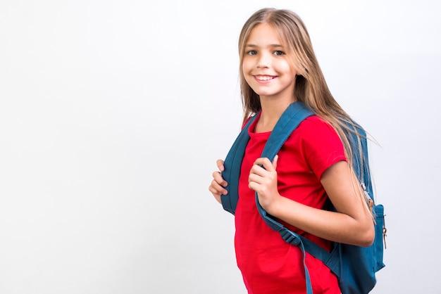 Glimlachend schoolmeisje dat zich met rugzak bevindt