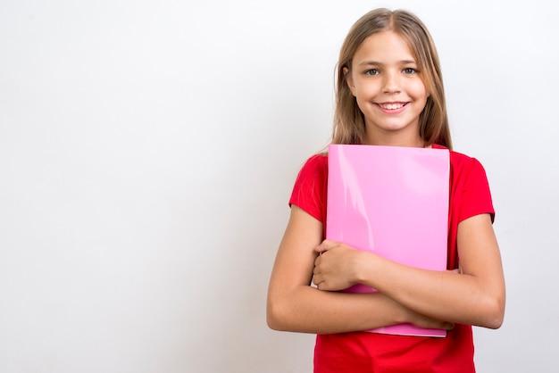 Glimlachend schoolmeisje die voorbeeldenboek dragen