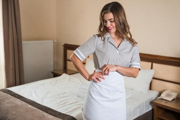 Glimlachend schoonmaakmeisje die zich dichtbij het bed in de hotelslaapkamer bevinden