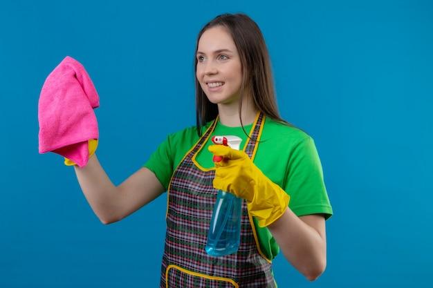 Glimlachend schoonmakend jong meisje die eenvormig in handschoenen dragen die schoonmakende hulpmiddelen en doek op geïsoleerde blauwe achtergrond houden