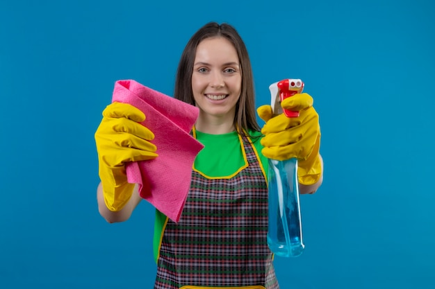 Glimlachend schoonmakend jong meisje die eenvormig in handschoenen dragen die schoonmakende nevel en vod standhouden aan camera op geïsoleerde blauwe achtergrond