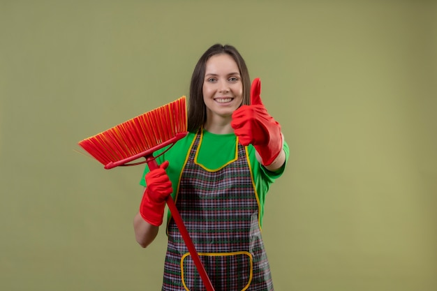 Glimlachend schoonmakend jong meisje die eenvormig in rode handschoenen dragen die haar duim op geïsoleerde groene achtergrond dweilen