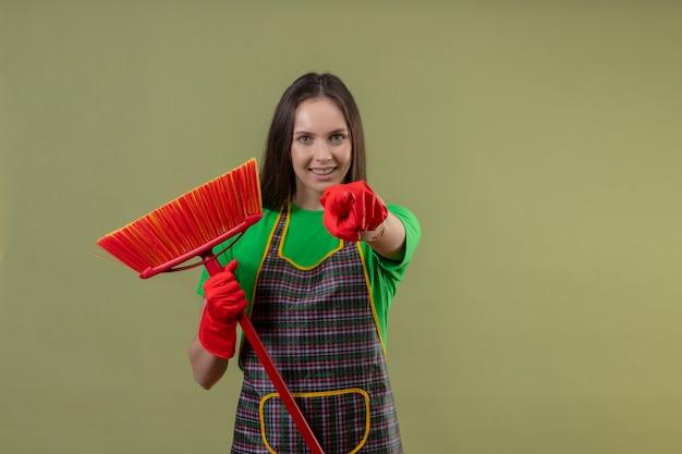 Glimlachend schoonmakend jong meisje die eenvormig in rode handschoenen dragen die zwabber houden die u gebaar op geïsoleerde groene achtergrond tonen
