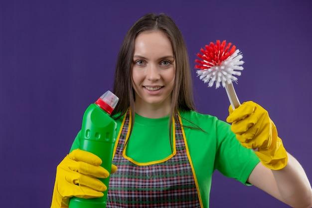 Glimlachend schoonmakend jong meisje die uniform in handschoenen dragen die reinigingsmiddel en borstel op purpere achtergrond houden