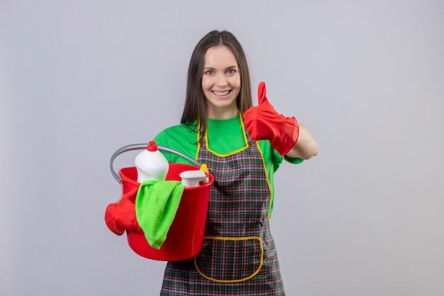 Glimlachend schoonmakend jong meisje die uniform in rode handschoenen dragen die schoonmakende hulpmiddelen haar duim op geïsoleerde witte achtergrond houden