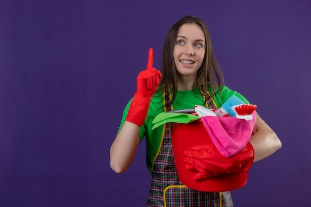Glimlachend schoonmakend jong meisje die uniform in rode handschoenen dragen die schoonmakende hulpmiddelen houden wijst vinger omhoog op geïsoleerde purpere achtergrond Gratis Foto