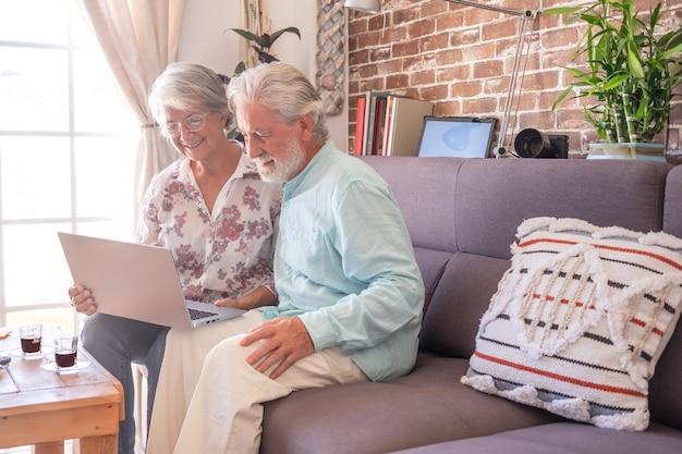 Glimlachend senior koppel op de bank thuis met behulp van laptopcomputer die pauze heeft met koffie-espresso