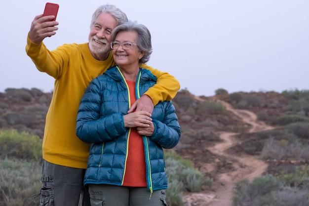 Glimlachend senior koppel op het platteland dat een selfie maakt met mobiele telefoon. zorgeloze senioren casual gekleed genieten van excursie in bergvoetpad