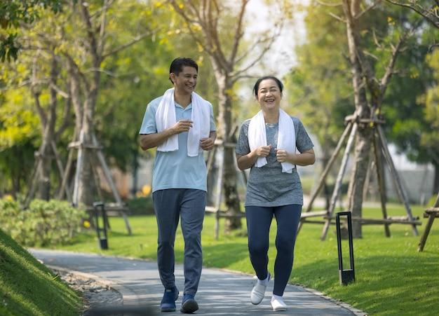 Glimlachend senior paar joggen, senior paar joggen en hardlopen in het park buiten de natuur
